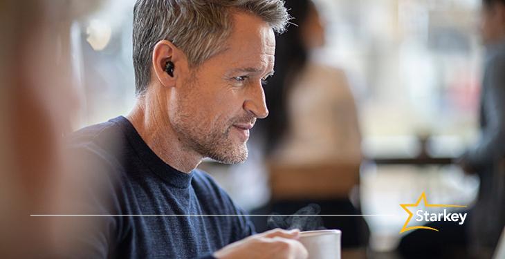Man wearing the Starkey Livio Edge AI Custom Hearing Aids in a coffee shop